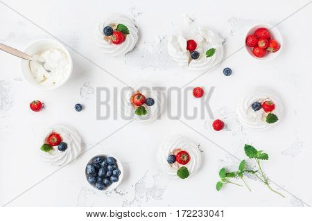 Meringues Pavlova cakes with strawberry and blueberry. Flat lay top view