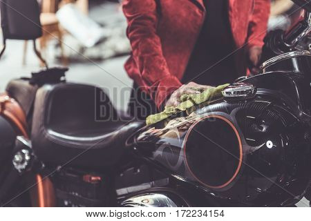 Focus on hand of retiree polishing her motorcycle in comfortable garage
