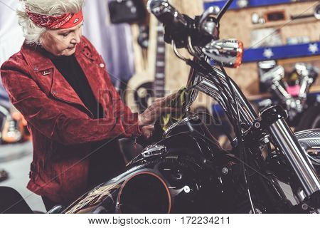 Serene old female cleaning her bike in cosy mechanic shop