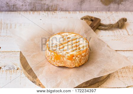 Whole wheel of soft French,German cheese with orange rind with mold on parchment paper, wood cutting board, concrete wall rustic kitchen interior