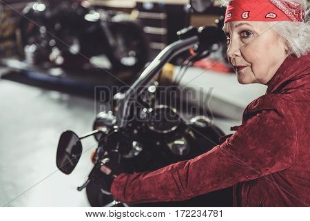 Calm old woman sitting on motorcycle while pensioner riding from wide garage