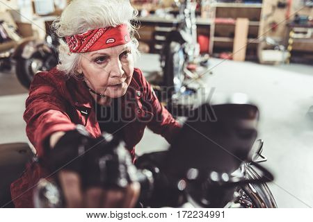 Cool old female pensioner riding bike while leaving mechanic shop