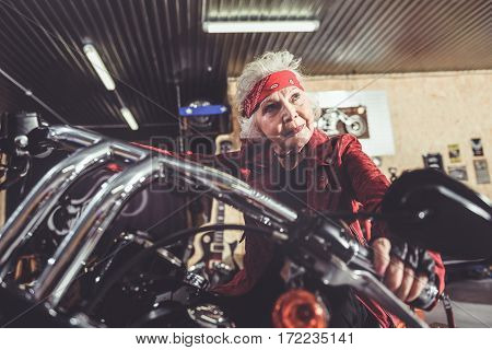 Outgoing old woman leaving wide mechanic shop while riding on bike
