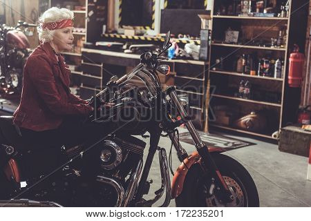 Outgoing grandmother sitting on bike while leaning her hands on frame of it in wide mechanic shop