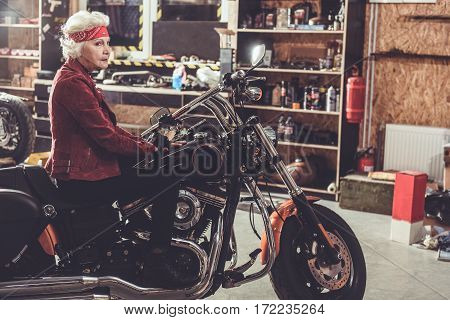 Smiling grandmother situating on motorcycle near shelves with instruments in wide mechanic shop