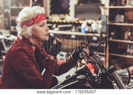 Serene old woman rouging lips by lipstick while looking at mirror and sitting on bike in garage