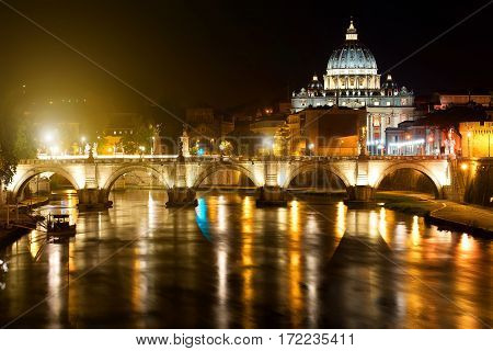 Night view on the Sant' Angelo Bridge and Basilica of St. Peter in Rome, Italy