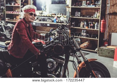 Smiling grandmother wearing dark glasses and sitting on motorcycle while leaning her hands on leg in wide mechanic shop