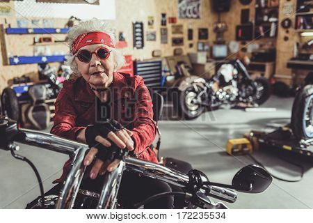 Serene old woman leaning on motorcycle while sitting on it in mechanic shop