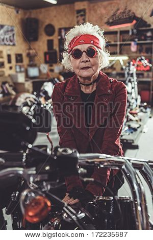 Satisfied female retiree leaning on frame of motorcycle in mechanic shop
