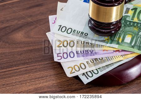 Judge wooden hammer with many euro bills on desk.