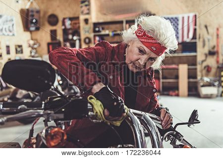 Serene grandmother polishing motorcycle in bright wide mechanic shop