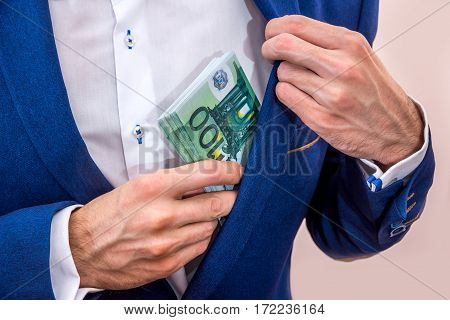 Businessman Putting 100 Euro Bills In His Pocket.