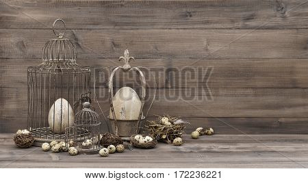 Easter decoration with eggs nest and birdcage. Vintage still life