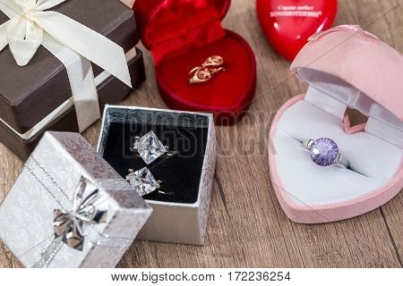 Lot Of Gift Boxes With Gold Jewelry On The Table.