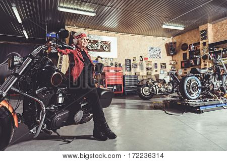 Cheerful old woman leaning on motorcycle while standing in mechanic shop