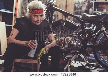 Cool old woman burnishing motorcycle while situating on small chair in mechanic shop