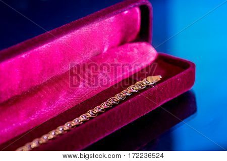 Gold bracelet in red gift packing isolated on dark blue.