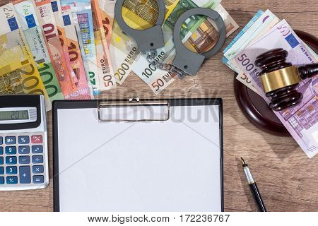 Gavel,handcuffs And Euro Money With Empty Notepad On Desk. Criminal Concept.