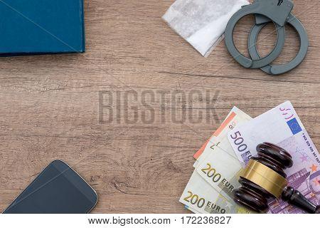 handcuff ueros drug and phone on desk.