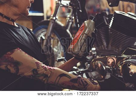 Old woman want to grease her bike by engine oil in cozy mechanic shop