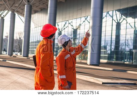team of young engineers discussing a construction project. The wear overalls and safety helmets. Business modern background