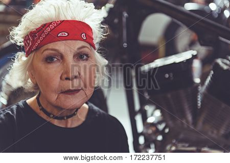 Focus on serious face of female retiree making machine maintenance in mechanic shop