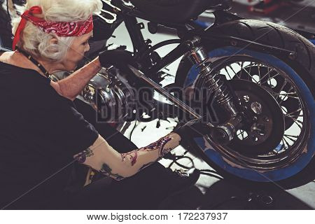 Serene female pensioner doing motorcycle maintenance with ratchet wrench in mechanic shop