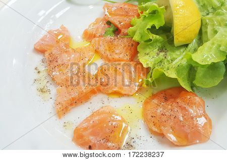Raw salmon slices drizzled with lemon oil and pepper