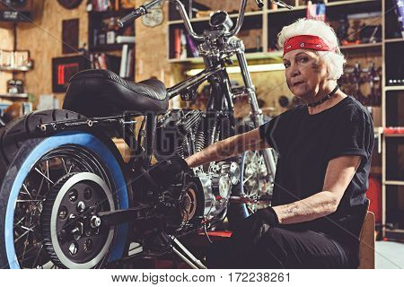 Calm grandmother reconditioning motorcycle while sitting on chair next to it in garage