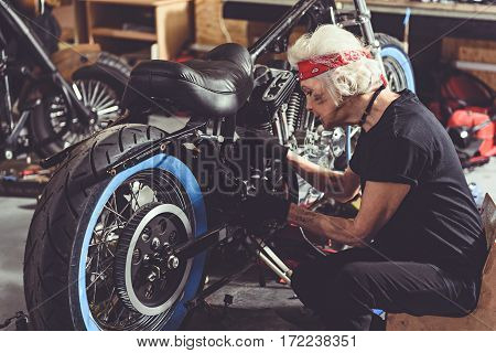 Serene female pensioner repairing bike while situating on seat near it in cozy garage