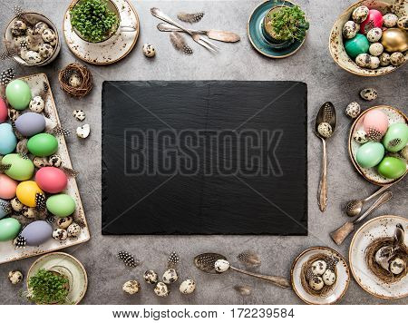 Easter table decoration with colored eggs. Holidays background stone plate and space for your recipe text