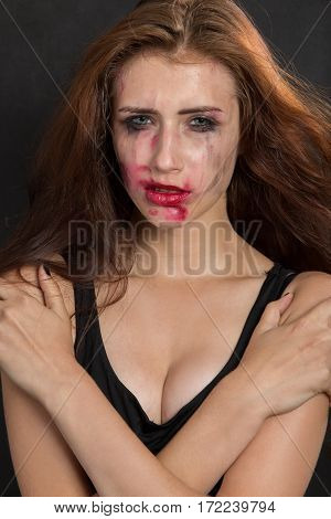 beautiful sad woman with smeared cosmetics on black background