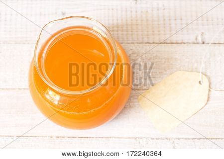 Fresh carrot juice in a glass jar with the blank label