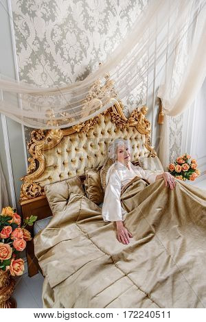 Top view of happy old woman lying on expensive bed at her apartment. She is looking forward and smiling