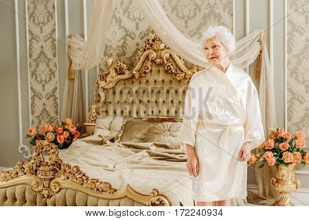 Pensive mature lady is standing alone in classic bedroom. She is looking aside with melancholy