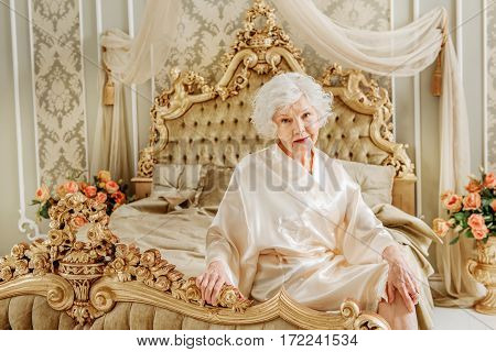 Elegant old queen is sitting on expensive bed and looking at camera with calmness