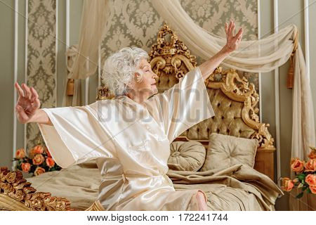 Sleepy senior woman is sitting on bed and stretching arms sideways. Her eyes are closed with relaxation