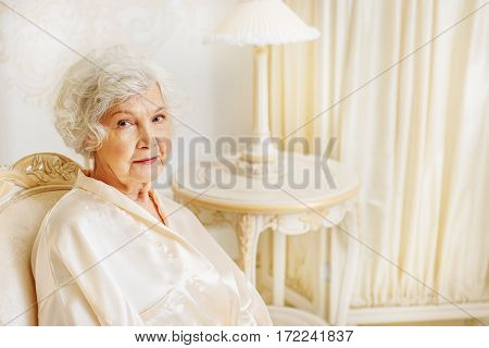 Calm senior lady is resting on chair in her gorgeous bedroom. She is looking at camera with tranquility