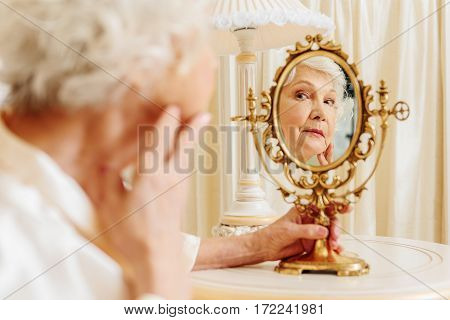 Rich old sad maid is observing her wrinkles in mirror. Focus on her reflection
