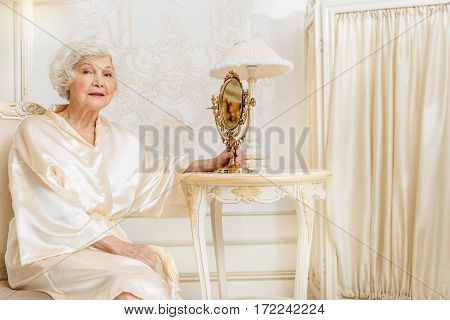 Elegant old woman is satisfied with her appearance. She is holding mirror and smiling
