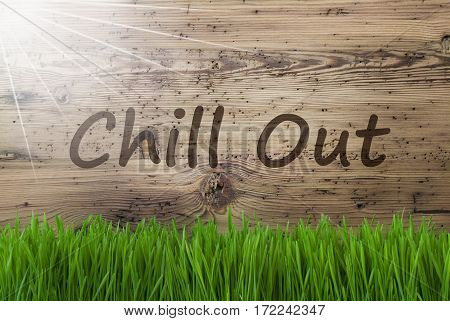 English Text Chill Out. Spring Season Greeting Card. Sunny Aged Wooden Background With Gras.