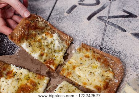 The Female Hand Takes A Slice Of Pizza Four Cheese With Oregano And Olive Oil. Quattro Fromaggi