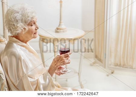 Where is my youth. Sad old lady is drinking wine while sitting on armchair in luxurious room