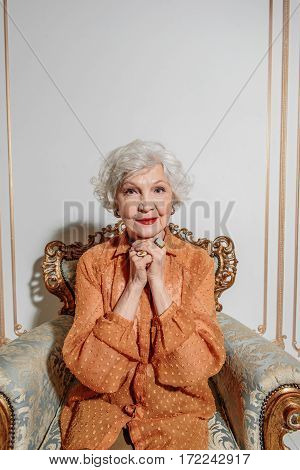 Cheerful old woman is waiting for someone at home. She is sitting on chair and looking forward with hope