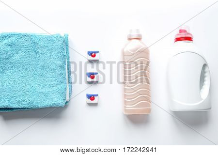 Bright clean towels pile with detergent and plastic conditioner bottles in laundry background top view