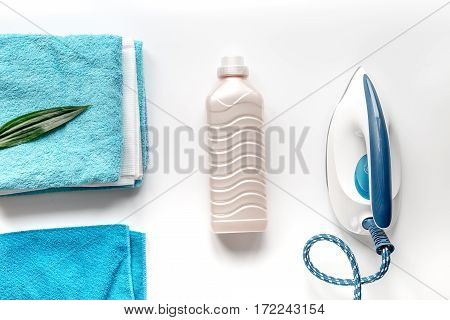 housekeeping set with towels and iron in laundry on white desk background top view