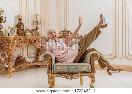 Life is great. Happy senior woman is relaxing on confortable chic armchair in her gorgeous apartment. She is raising hands up and laughing