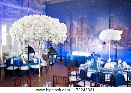 Wedding. Banquet. The chairs and table for guests, served with cutlery and crockery and covered with a blue tablecloth