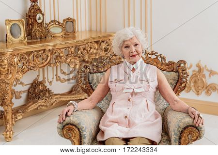 Sophisticated senior woman is resting on gorgeous chair at her chic apartment. She is looking at camera with seriousness